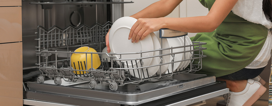 Woman loading dishwasher in kitchen