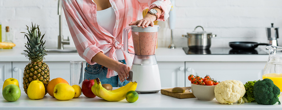 Woman preparing a smoothie in a blender