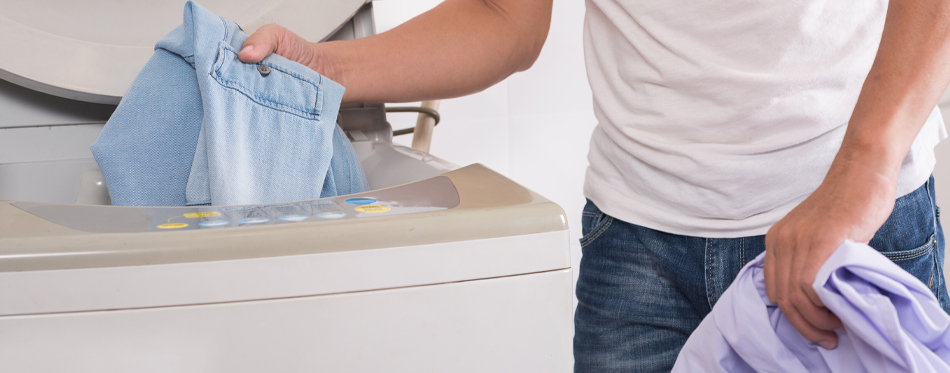 putting clothes in dryer